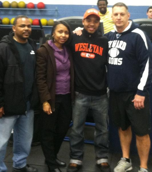 Howard running back Michael Anderson (West Virginia Wesleyan) flanked by his parents (left) and coach Bruce Strunk (right) Feb. 6 at Howard High.