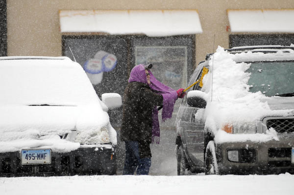 A woman brushes snow off her car in a Dunkin' Donuts parking lot in Middletown during Friday's snowfall.