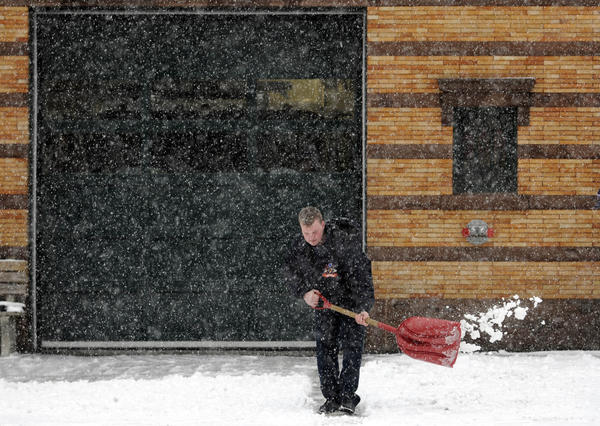 Middletown firefighter Nick Barnych of Hamden shovels snow in front of fire headquarters on Main Street. Barnych was among a group of about two dozen firefighters manning the firehouse on a 24-hour shift. They brought in about twice the normal number of staff to be ready to respond to emergencies during the blizzard that is expected to dump about two feet of snow on most parts of the state.