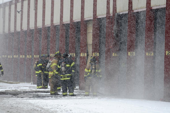 Hartford Firefighters stand outside a shed where a truck caught fire at the Hartford city garage Friday afternoon. One truck was damaged in the fire.