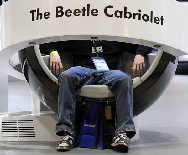 An attendee gets a comfortable seat to view a commercial video of the Beetle Cabriolet at the 105th Chicago Auto Show held at McCormick Place in Chicago.