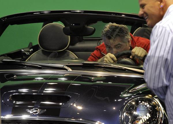 An attendee gives it his all while being filmed on a Mini Cooper at the 105th Chicago Auto Show held at McCormick Place in Chicago