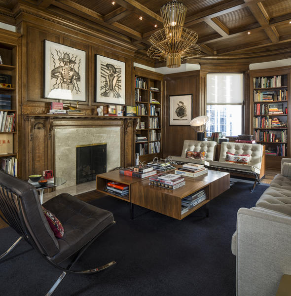 The wood-paneled living room with fireplace contains part of the homeowners' collection of 3,000 books; here they've organized about 1,200 related to art and architecture.