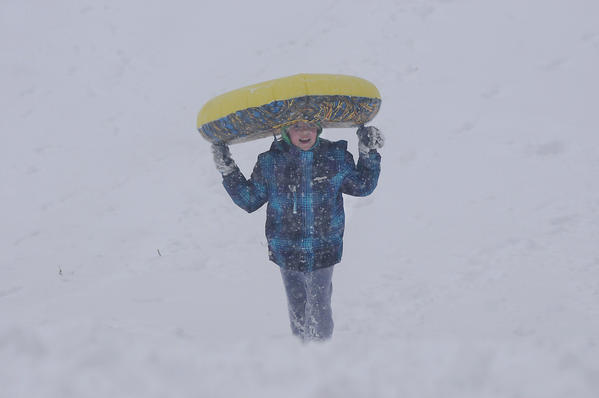 "Emmerson Gendron, 10, of New Britain makes her way up the hill at Walnut Hill Park during the snowstorm Friday. Her mom and dad, Patricia and Chad Gendron, had their first date on this snowy hill back in March, 1996, with Chad pushing Patricia down a hill in a tube just like the one Emmerson carries here. ""He flipped me over,"" she said. They call it ""returning to the scene of the crime,"" she said."