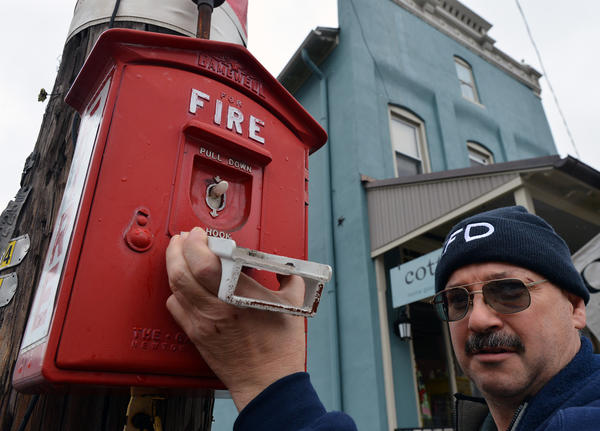 Emmaus Fire Department Chief James Reiss stands near a fire alarm box on 4th St. in Emmaus. Emmaus has about 30 of the old-fashioned Gamewell fire alarm call boxes throughout the borough, hanging on utility poles or in buildings.