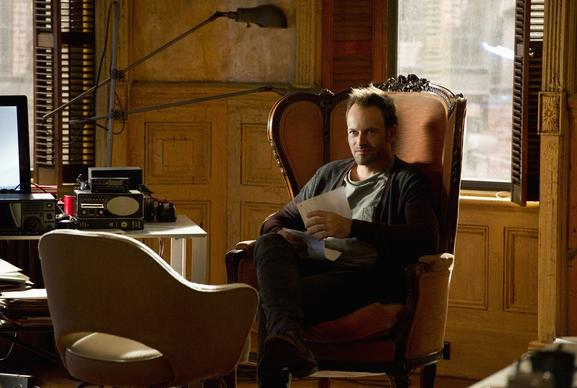 Sherlock Holmes (Jonny Lee Miller) settles into a wingback chair in a dilapidated brownstone owned by his father.