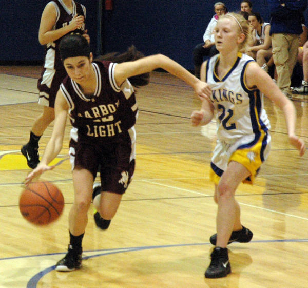 Harbor Light Christian's Annie Fila (left) drives to the basket against Alanson during Thursday's Northern Lakes Conference contest at the Alanson High School gym. The Swordsmen defeated the Vikings, 49-34.