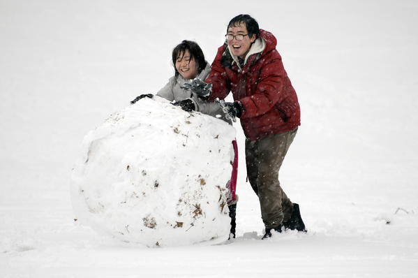 Mao Misaki, left, a student from Japan, and her friend Hamin Kim of Stratford struggle to push a giant ball of snow on the field below Foss HIll at Wesleyan University where the two are sophomores, during Friday's snowstorm. They were planning on making it big enough to carve out to make an igloo, but admitted that they were going to have to call some friends to come and help soon as the ball was getting too heavy to manage.