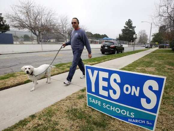 "A man walks his dog across the street from Jefferson Elementary School past a ""Yes on S"" sign."