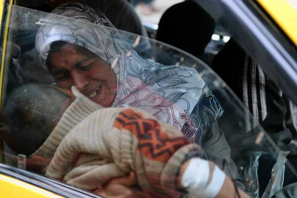 A woman holds her injured son as they arrive by taxi at a hospital in the northern Syrian city of Aleppo.