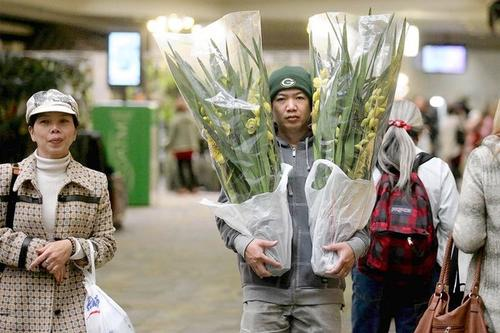 Peter Dinh, right, of Santa Ana carries two cymbidium orchids as he and his sister Thoa Dinh, left, attend Newport Harbor Orchid Society's 12th annual Orchid Expo and Sale at Westminster Mall on Friday.