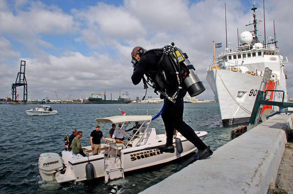 A member of the Broward Sheriff's Office Dive team jumps in the water near the Coast Guard Cutter Tampa.  They were conducting a training exercise at Port Everglades.