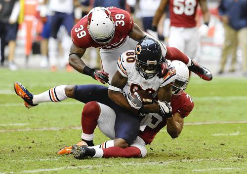 Earl Bennett is tackled by the Cardinals' Kerry Rhodes and James Sanders.