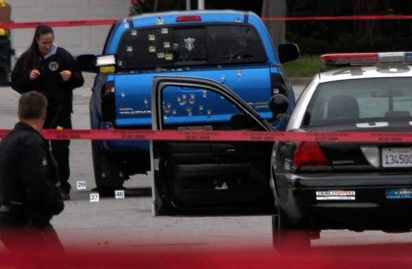 Police investigators examine a blue pickup truck riddled with bullets on Redbeam Avenue in Torrance. Officers, thinking shooting suspect Christopher Dorner might have been in the vehicle, unleashed a fusillade, wounding a woman and her mother.