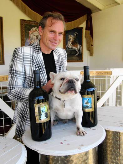 Jean-Charles Boisset, head of Boisset Family Estates, stands for a photograph with his French bulldog, Frenchie, at Frenchie Winery in St. Helena, California,