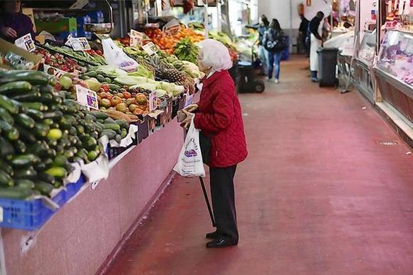 A woman looks at fruits and vegetables at a market stall in Madrid