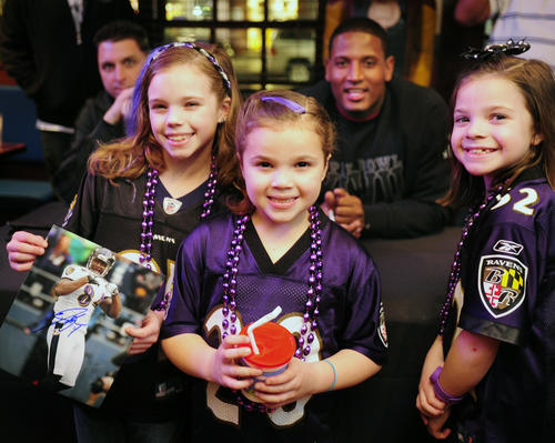 Singing sensations and YouTube stars Emma, Ava and Maddie Ingrassia are all smiles as they pose for a photo with Baltimore Ravens tight end Ed Dickson Friday night at the Dark Horse Saloon in Bel Air.