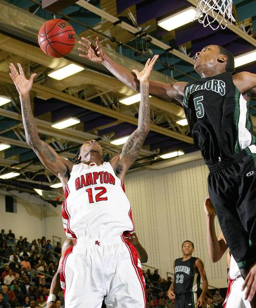 Rob Ostermaier/Daily Press Photo Rodney Bullock of Kecoughtan knocks the rebound wawy from Anthony Barber of Hampton during the second half Friday at Woodside.
