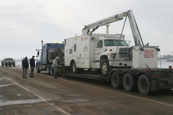 A replacement de-icer truck is seen still loaded on a semi after  it arrived at the Aberdeen Regional Airport from Omaha, Neb. Both the malfunctioning truck and the replacement truck are owned by Delta Global Services, a subsidiary of Delta Air Lines.