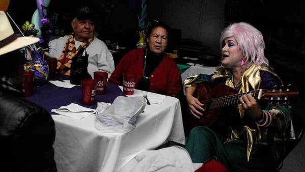 Musician Paty Hurtado plays acoustic guitar in the dark to seniors at the Calexico senior Mardi Gras, which continued despite power outages in the city Friday.