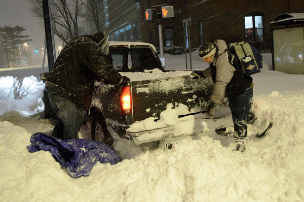 David Echevaria of Hartford, at right, helps two friends attempt to get a pickup truck out of a snow bank near the intersection of Farmington Ave. and Sigourney Street in Hartford.