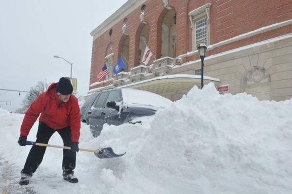 Richard Wiszniak, of Wethersfield, digs his SUV out of a snowbank in front of the Bushnell Theater Saturday morning.