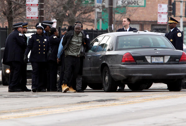 Chicago Police officers handcuff a man who was involved in an altercation outside the Greater Harvest Baptist Church before the funeral for 15-year-old Hadiya Pendleton in Chicago on Saturday, Feb. 9, 2013.(John J. Kim /Chicago Tribune)