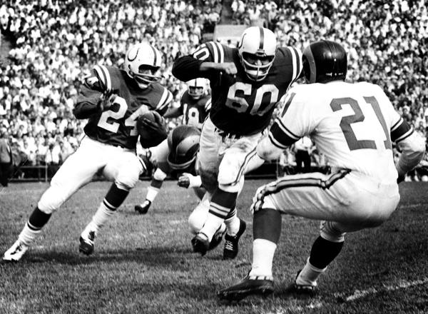 In October of 1960 at a Colts game George Preasis, #60, blocks Ed Meador, Ram defensive halfback, right, to help the Colts' Lenny Moore, #24, around right end in the scoreless first period.
