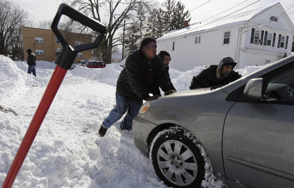 Good Samaritans Ray Shelton, left, Angel Cortes and Jose Roman, right, together push a stuck motorist out of a snow bank on Burnside Avenue in East Hartford Saturday afternoon. The three all live in East Hartford.
