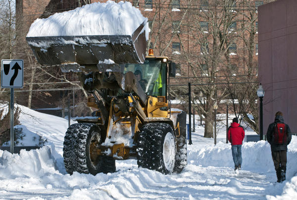 A front-end loader clears snow from the UConn campus in Storrs after this weekend's historic snowstorm dropped 20 to 36 inches.