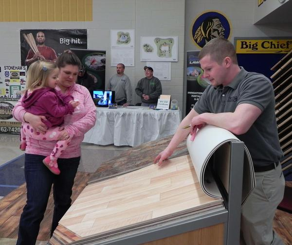 Victor Morningstar, Waynesboro Floor Covering, shows Kristen Jones and her daughter Morgan, 2, of Wayneboro, floor coverings at Saturday's 17th annual Greater Waynesboro Chamber of Commerce Business Expo at the Waynesboro Area Senior High School.