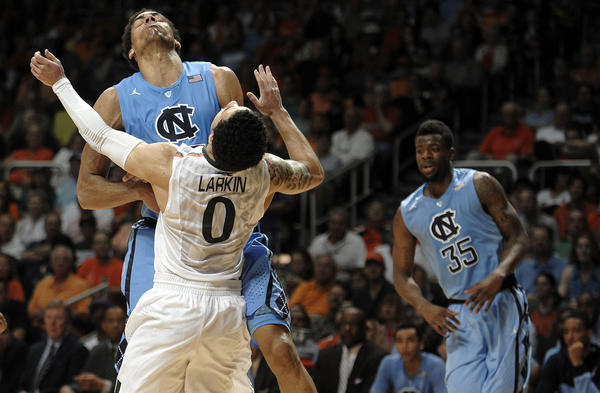 Miami guard Shane Larkin draws a foul from North Carolina forward James Michael McAdoo during the second half of their game