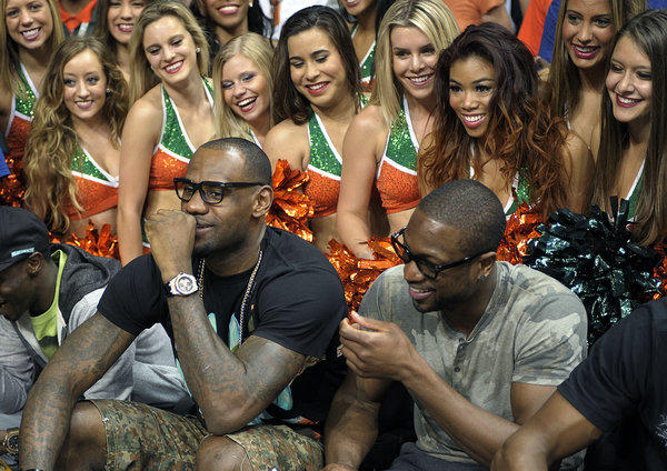 University of Miami dancers try to get their pictures taken with Miami Heat starts LeBron James and Dwyane Wade during halftime of the Hurricanes game against the North Carolina Tar Heels.