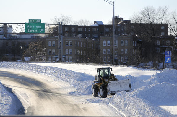 A Connecticut Department of Transportation driver clears snow from the I-84 West viaduct in Hartford Saturday afternoon.