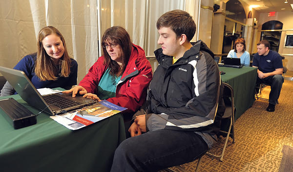 Kristin Brezler, left, assists Melinda Staubs and her son Daniel Greenwood with filing of federal forms for college applications. Brezler is director of financial aid at Kaplan University in Hagerstown. Also working on forms are Sandy Cumings and Kaplan University financial aid officer Luke Meyers. The assistance for families was presented by volunteers Saturday at Valley Mall.