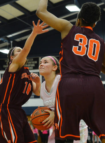 Moravian's Alesha Marcks (25) looks to make a shot against Susquehanna's Ainsley Rossitto (10) and Candence Cannady (30) during a women's basketball game on Saturday. Marcks is from Northampton. It was Pink Zone Day for women to help raise funds to donate to the Kay Yow Cancer Fund.