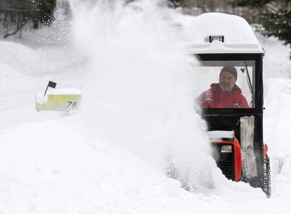 Paul DeCarlo uses a snow blower to clear the walk in front of his Greenfield, Mass., home.