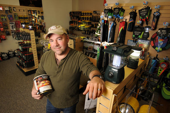 "Bob Harris is president and CEO of Harris Outdoors, an Old Saybrook store that sells fishing, hunting, camping and outdoors equipment. He also caters to ""preppers,"" people who are prepared for disasters. He is holding a can of freeze-dried chicken that has a 25-year shelf life."