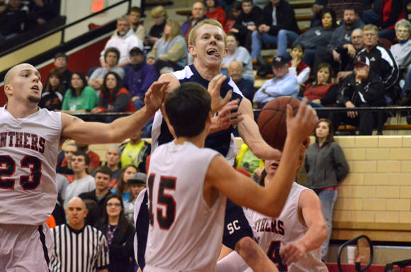 Scott City senior Brett O'Neil attempts to drive past Great Bend defenders Ethan Henderson (23), Dillon Reiser (15), and Shade Wondra (24).