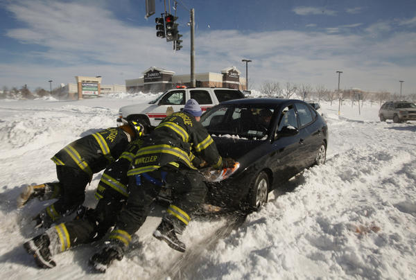 Members of the Nissequogue Fire Department assist a stranded motorist in Suffolk County, N.Y., where a group of people took shelter at a Wal-Mart store.