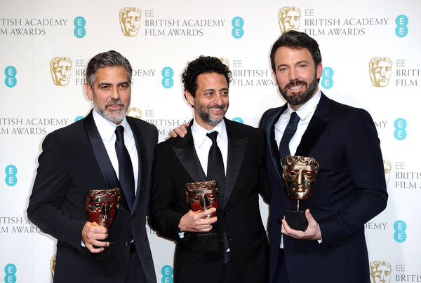 "Producers George Clooney, left, Grant Heslov and Ben Affleck celebrate backstage in London on Feb. 10, 2013, after their movie ""Argo"" was named best film at the BAFTA awards."