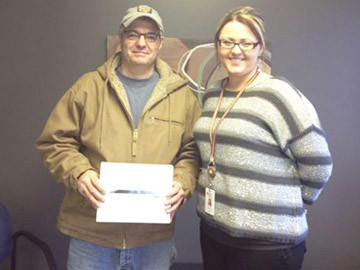 Butch Jangula, left, of Aberdeen received an iPad from Molly Vetter, the manager of United Blood Services in Aberdeen. Jangula was one of three door-prize winners during the 2012 Battle of the Badges, sponsored by UBS.