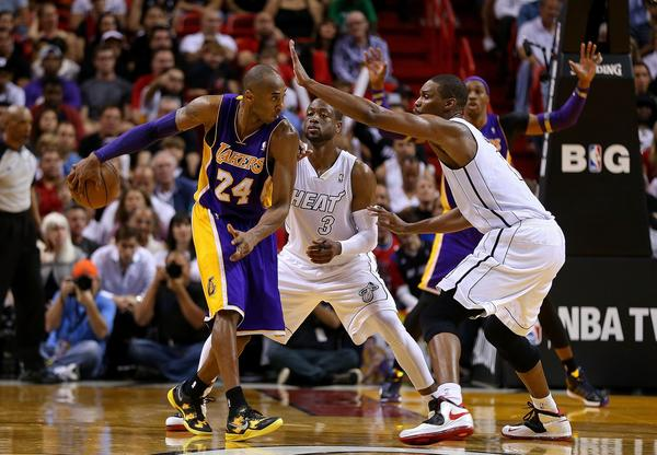 Lakers guard Kobe Bryant wraps a no-look pass behind his back to Dwight Howard (background) on Sunday, circumventing the defense of the Miami Heat's Dwyane Wade and Chris Bosh.