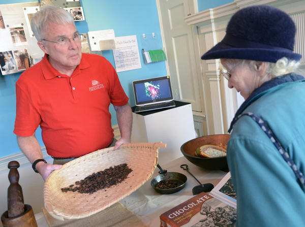 Doug Valkenburg, a volunteer from Mars Chocolate, demonstrates how to winnow the cocoa beans as Dolores Harris of Allentown looks on. Sweet Taste of History was held at the 1810 Goundie House in Bethlehem Sunday afternoon. Visitors are given a presentation where they are shown how chocolate was made in colonial times. They will be holding the program again on February 14.