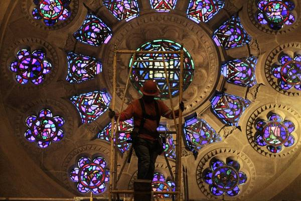 A worker removes the last bit of scaffolding in front of the restored rose window inside Wilshire Boulevard Temple. Philanthropist Erika Glazer, who came of age at the grand sanctuary, has pledged $30 million over the next 15 years toward the synagogue's ongoing restoration and redevelopment.