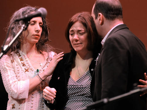 Bethany Yarrow comforts Francine Wheeler as her husband David leans in to kiss her after a concert at the Ridgefield playhouse Sunday afternoon with Peter Yarrow and a host of other musicians.