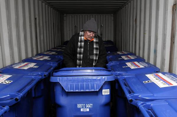 Volunteer Michael Lindley rolls a bin back into the Check-in Storage trailer at Venice Beach. The pilot program lets people retrieve their items between 3 and 5 p.m. daily.