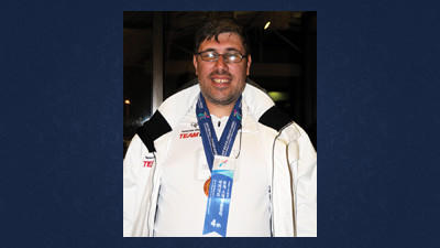 Cross-country skier Andy Sambol wears his medals and ribbons from the 2013 Special Olympics World Winter Games in the lobby of the Holiday Inn, Johnstown before the state winter games opening ceremonies.