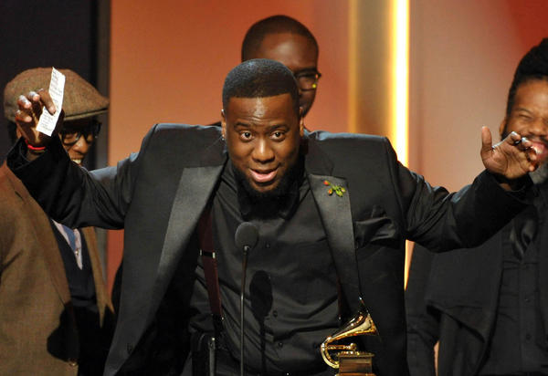 "Robert Glasper, center, accepts the award for R&B album for ""Black Radio"" during the Grammy Awards' pre-telecast Sunday in Los Angeles."