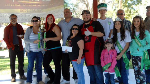 The Six Pack Crew, flanked by Carrot Festival officials and volunteers, shows its trophy for winning first prize in the Carrot Festival Family Cook-Off in Holtville on Sunday. The Six Pack Crew won $1,000 for their winning entry, pork carnitas.